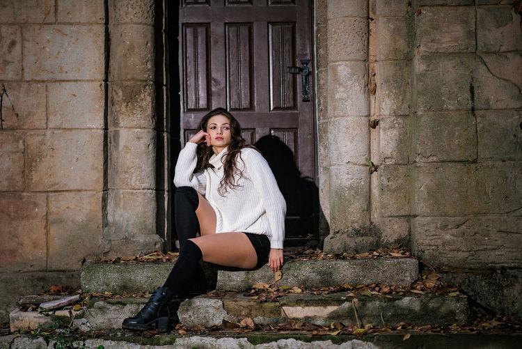 Portrait of woman sitting against building