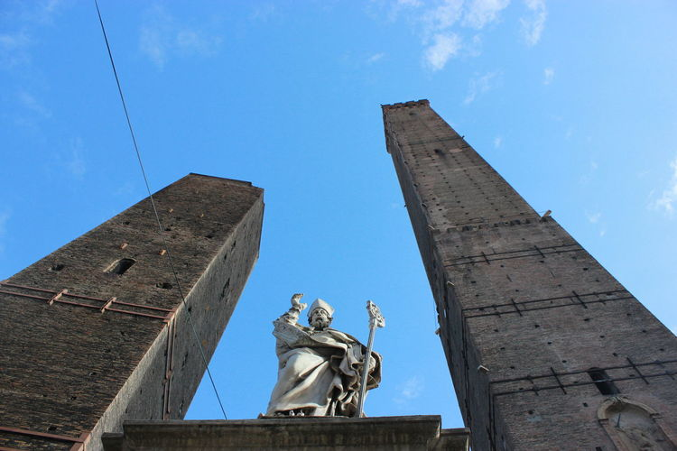 Low Angle View Of Statue Amidst Towers Against Blue Sky