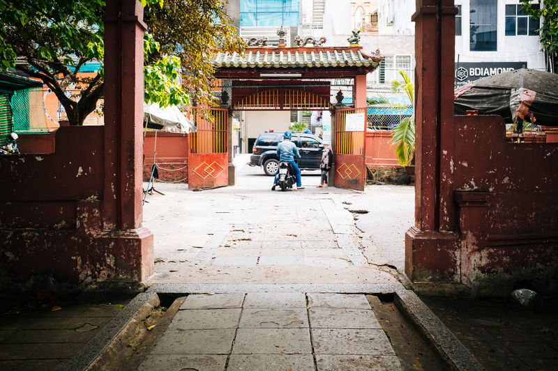 Gates Fujifilm_xseries Vietnam Ho Chi Minh City Saigon Architecture Built Structure Real People Building Exterior Day Men Building Rear View Full Length People City Transportation Nature Street Outdoors Lifestyles Mode Of Transportation Land Vehicle Plant