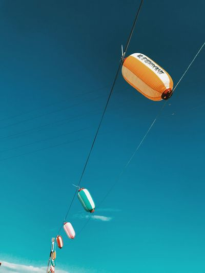 Low angle view of kite flying hanging against blue sky