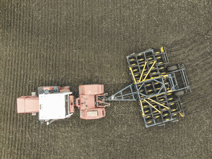 Aerial view of a modern tractor plowing dry field, preparing land for sowing Aerial Agriculture Field Tractor Farm Ground Soil Countryside Combine Machinery Motion Working Plowing High Angle View Directly Above Nature Land Industry Technology