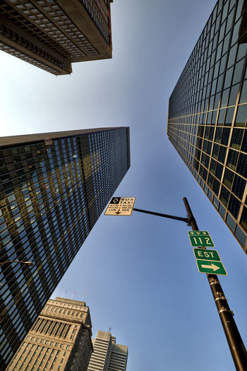 From below Colour Your Horizn Montréal Architecture Arrow Symbol Building Building Exterior Built Structure Canada City Communication Day Direction Guidance Low Angle View Modern No People One Way Outdoors Road Sign Sky Skyscraper Street Name Sign Text Western Script