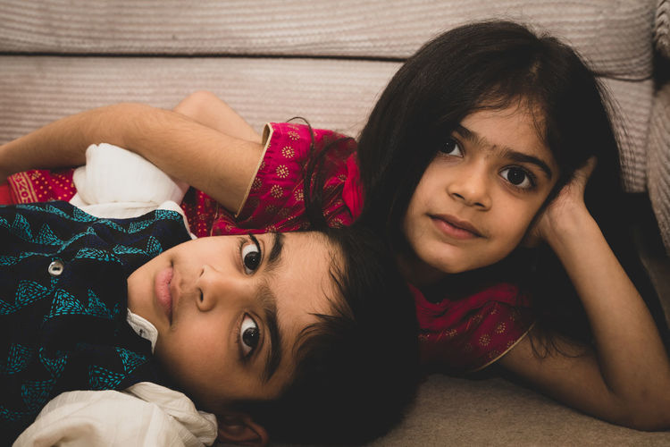 Portrait of cute siblings lying on sofa at home