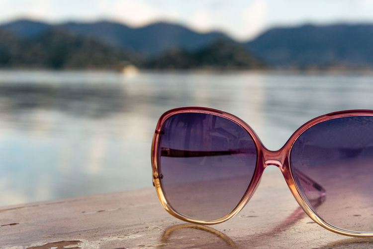 Women's fashionable sunglasses on a table top in front of Med sea side setting. Beach Close-up Day Eyewear Fashion Focus On Foreground Glasses Lake Land Nature No People Outdoors Personal Accessory Protection Reflection Security Still Life Sunglasses Sunlight Water