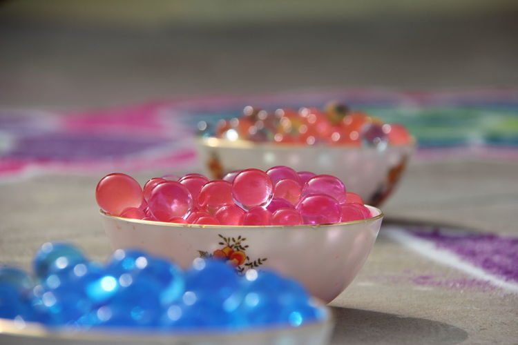 Close-up of colorful marbles in bowls on floor