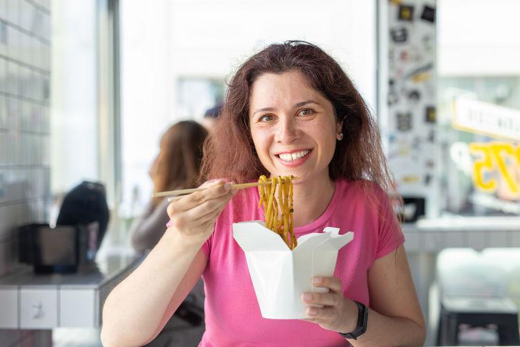 Portrait of smiling woman eating noodles