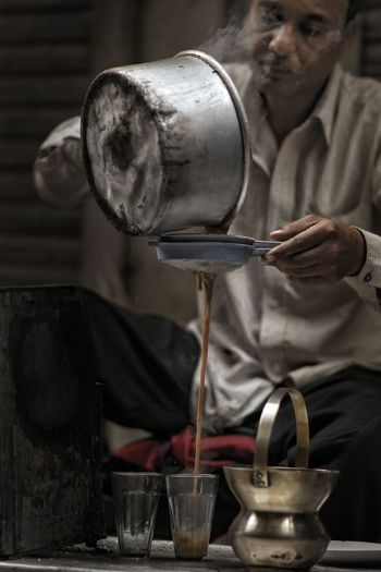 Close-up of man pouring tea in cup