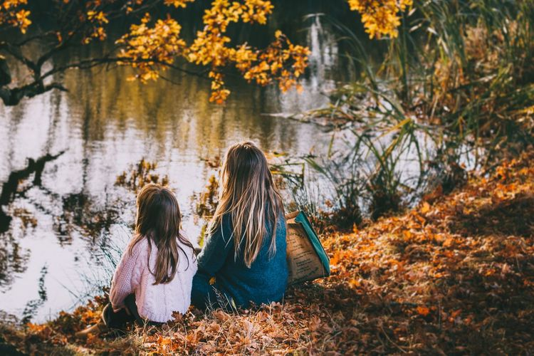Rear view of women sitting on footpath during autumn
