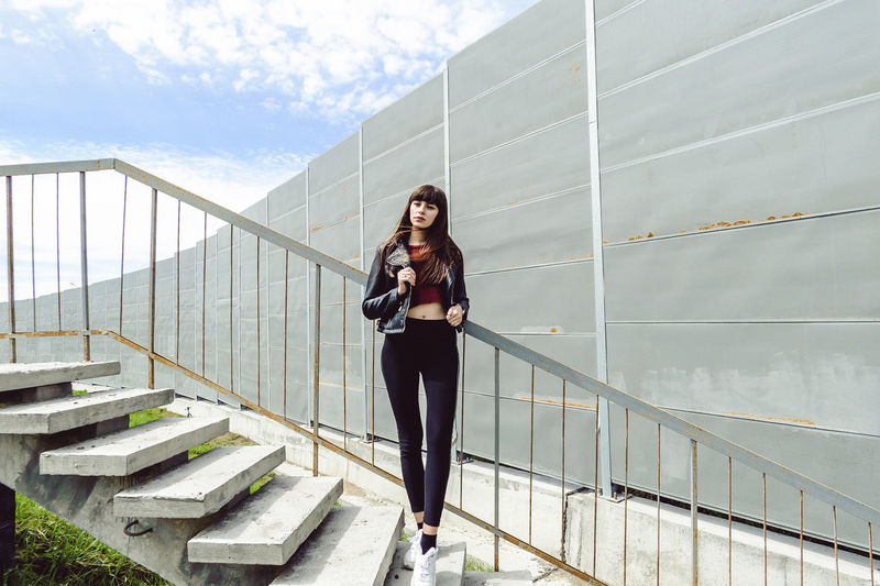 Thoughtful young woman standing on steps against wall