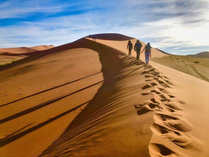 Rear View Of Friends Walking On Desert Against Sky