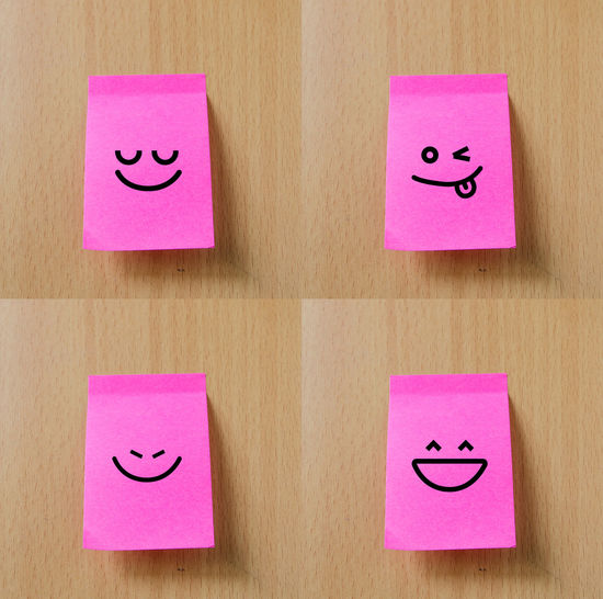 Close-up of smiley faces on pink adhesive notes over wooden table