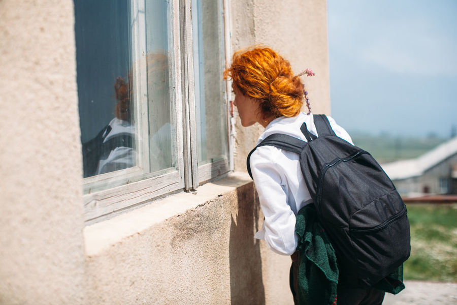 Girl looking in the window of an abandoned house Abandoned Abandoned Places Casual Clothing Curious Curiousity Day Female House Lifestyles Light And Shadow Looking Outdoors Redhead Sky Window