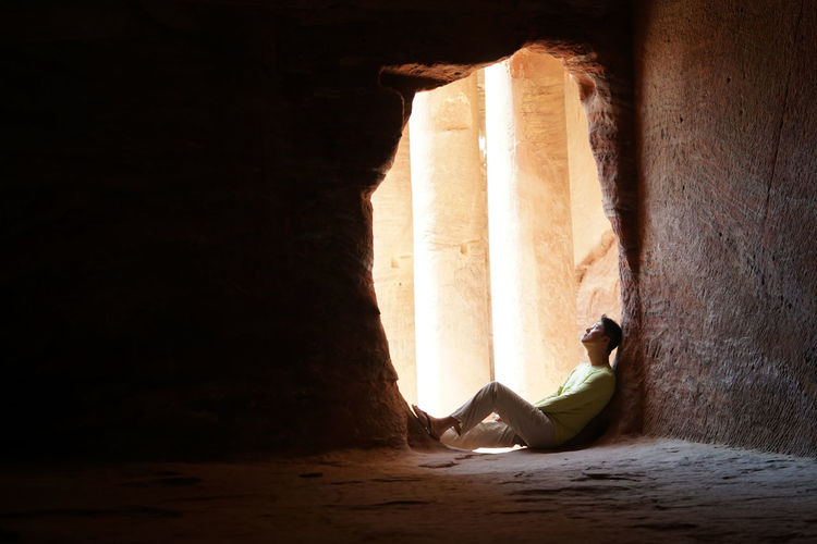 Man looking up while sitting in cave