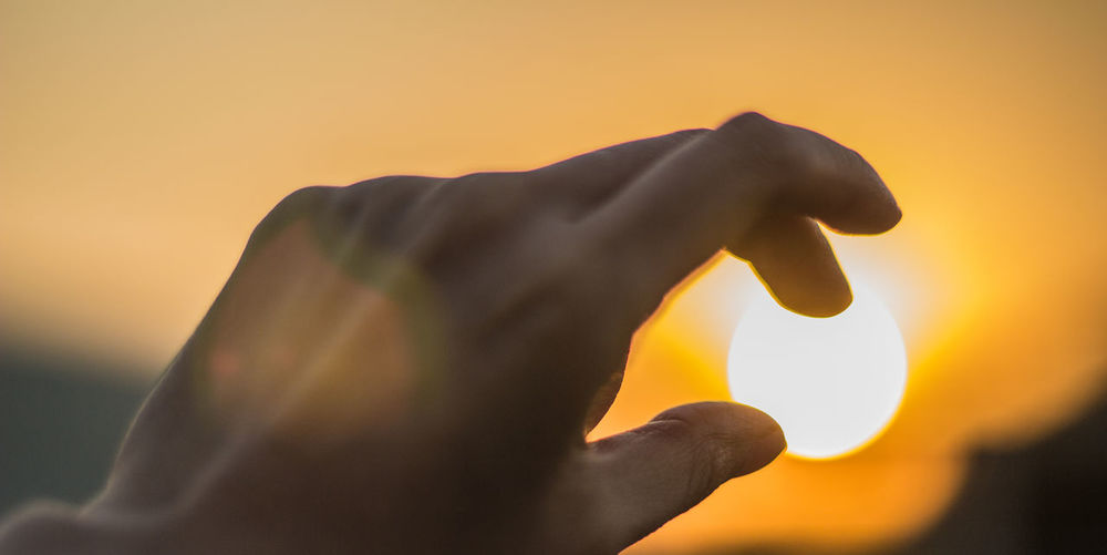 Close-up of hand against orange sky during sunset