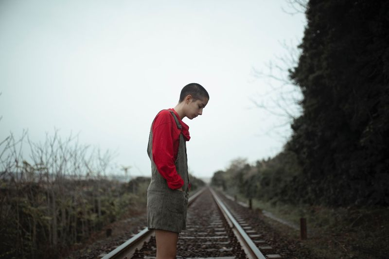 Side view of person standing on railroad track