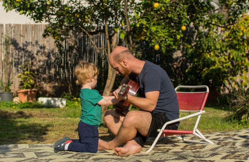 Full length of man teaching guitar to son in backyard