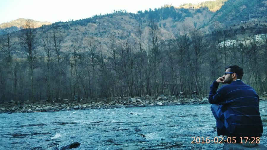 Sitting near River at Manali India watching Mountains and Trees