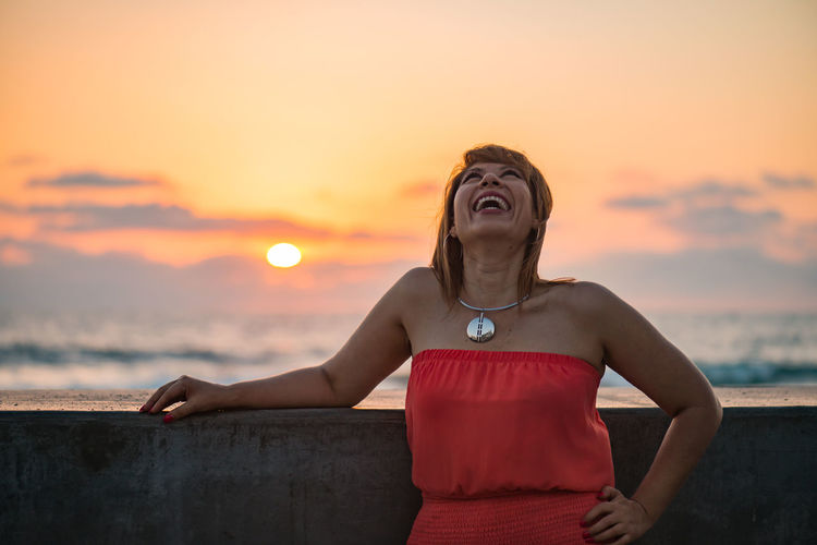 Woman laughing out loud, sunset behind her Atmospheric Mood Casual Clothing Cloud - Sky Dramatic Sky Focus On Foreground Front View Happy In Front Of Laughing Laughing Out Loud Orange Color Pretty Woman Relaxation Scenics Sea Sky Sun Sunset Tourism Tranquil Scene Tranquility Vacations Vibrant Color Water Woman Laughing