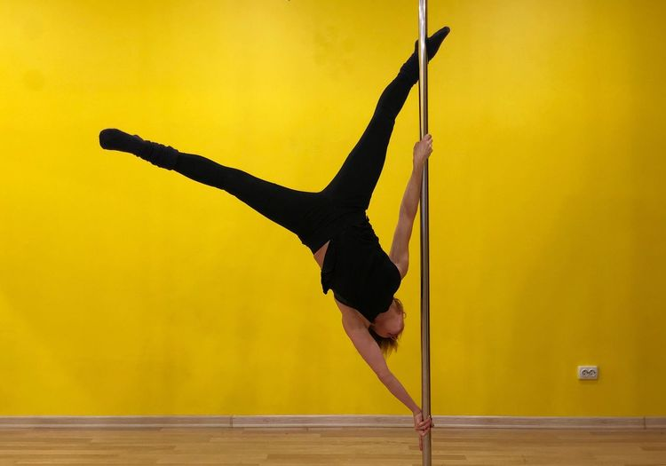 Full length of woman doing pole dancing against yellow wall