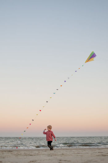 Boy at beach with kite flying against sky during sunset