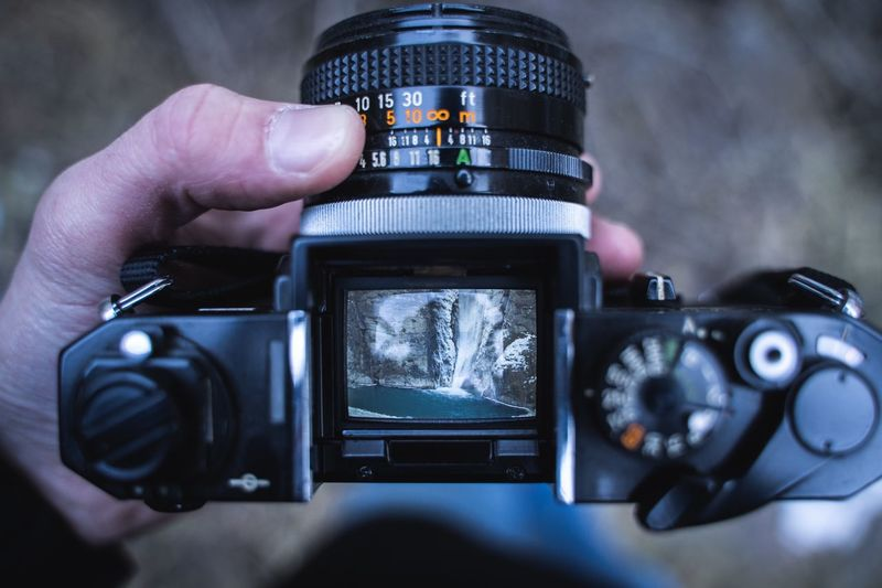 Close-up of human hand photographing waterfall with digital camera