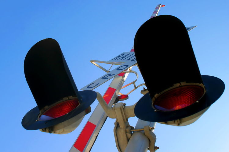 Rail Cro Railroad Crossing signal from below with sky in the background. Blue Caution Cross Crossing Danger Lights Rail Railroad Railway Red Safety Sign Signal Signs Sky Stop Symbol Traffic Train Trains Transport Transportation Travel Warning White