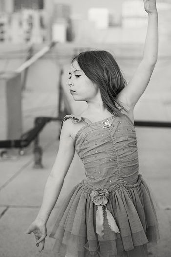 Girl dancing with arms raised