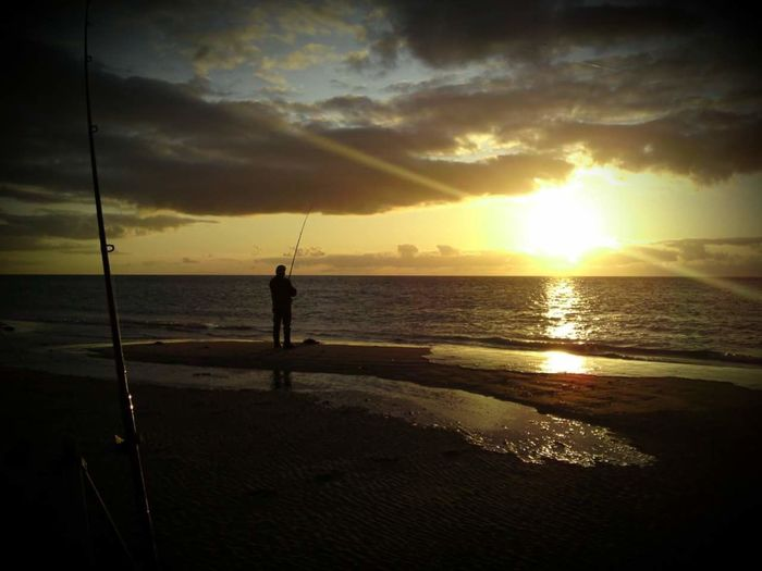 Man fishing on beach against sky during sunset