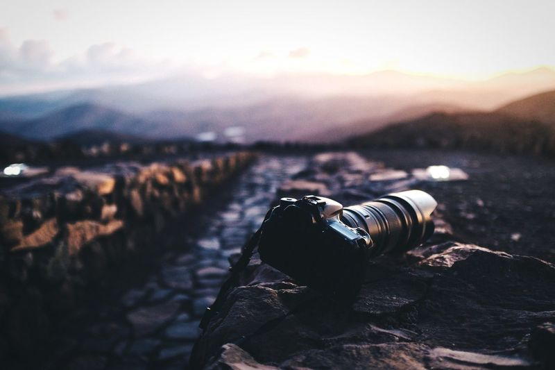 Digital camera on stone wall at sunset