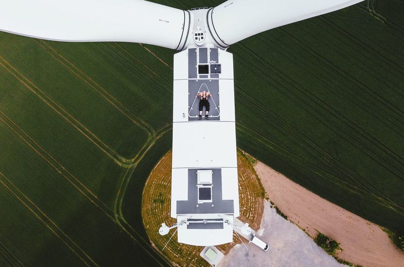 High angle view of man lying on wind turbine