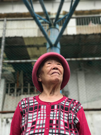 Low Angle View Of Thoughtful Senior Woman Looking Away While Standing Against Building