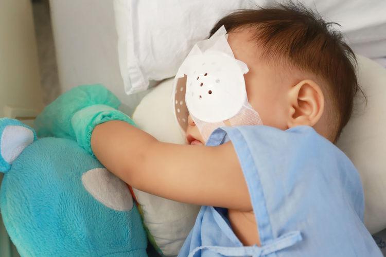 Cute boy with bandage on eyes sleeping in hospital