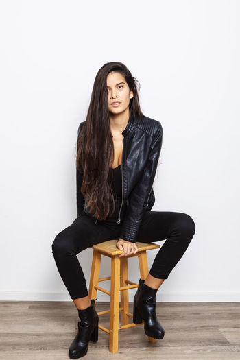 Portrait of beautiful young woman sitting on chair against wall