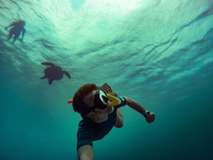 Low angle view of people snorkeling in sea
