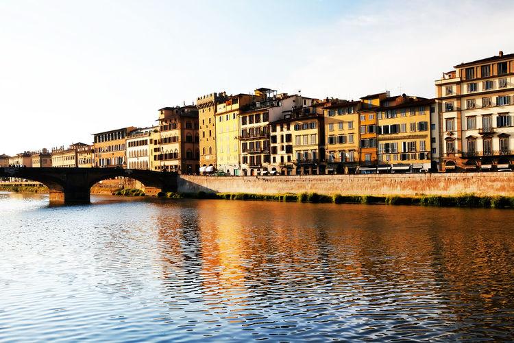 Ponte Santa Trinita Over Arno River By Buildings At Tuscany Against Clear Sky