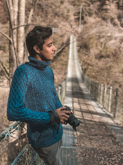 Young man looking away while standing on footbridge