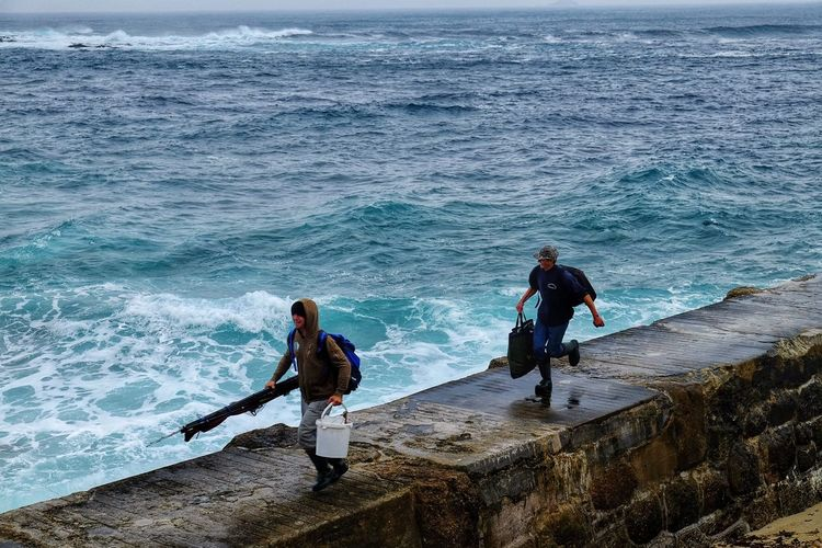 Full length of man fishing at sea shore