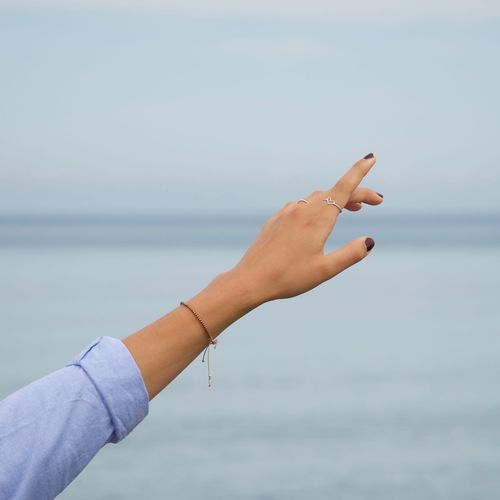 Cropped hand of woman against sea