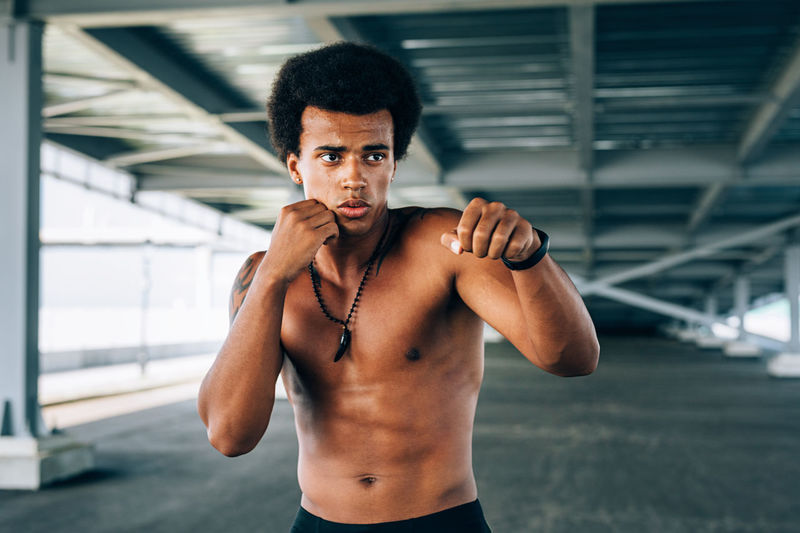 Shirtless male boxer exercising below bridge