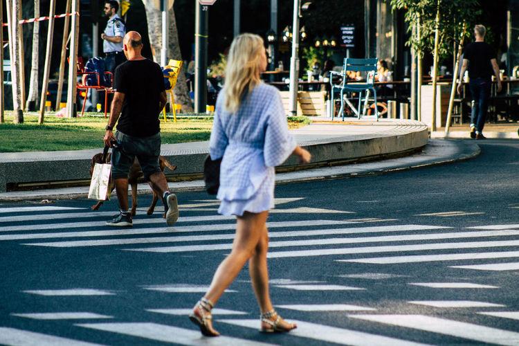 Rear view of people walking on road in city