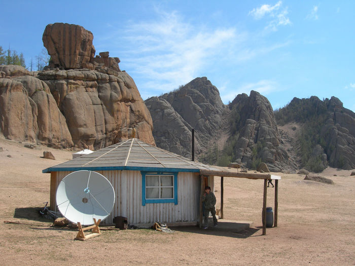 Woman By Hut And Satellite Dish On Field Against Rock Formations