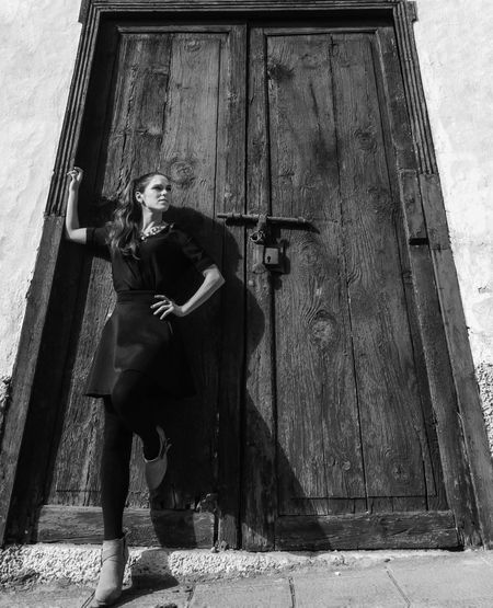 Full Length Of Woman Standing Against Closed Wooden Doors