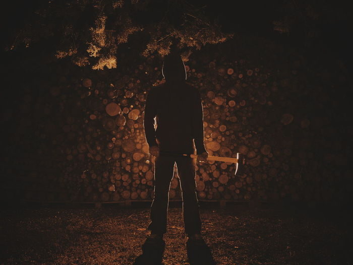 Full length of man standing with axe on field at night