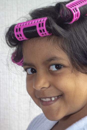 Portrait Of Girl With Hair Curlers Against Wall At Home