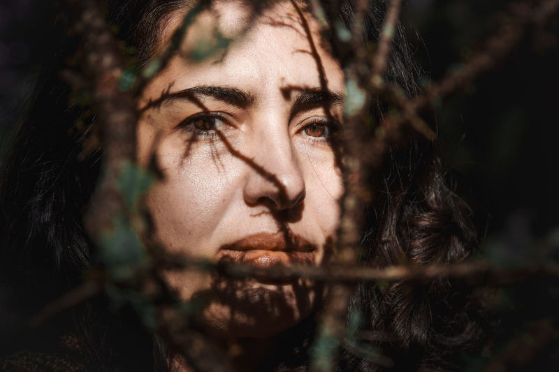 Portrait of a woman looking at camara between  branches in the forest