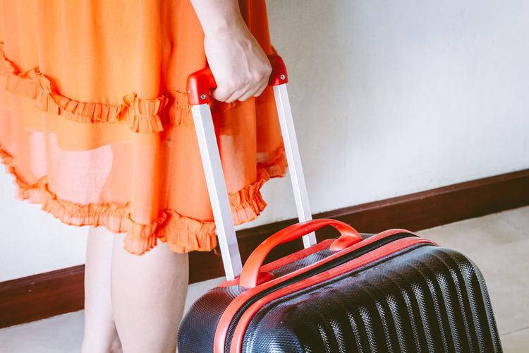 Woman holding suitcase Travel Traveling Adult Architecture Casual Clothing Clothing Day Focus On Foreground Holding Human Body Part Human Leg Indoors  Lifestyles Low Section Midsection One Person Orange Color Real People Red Standing Suitcase Women