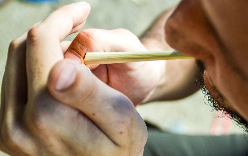 Close-Up Of Man Burning Marijuana Joint