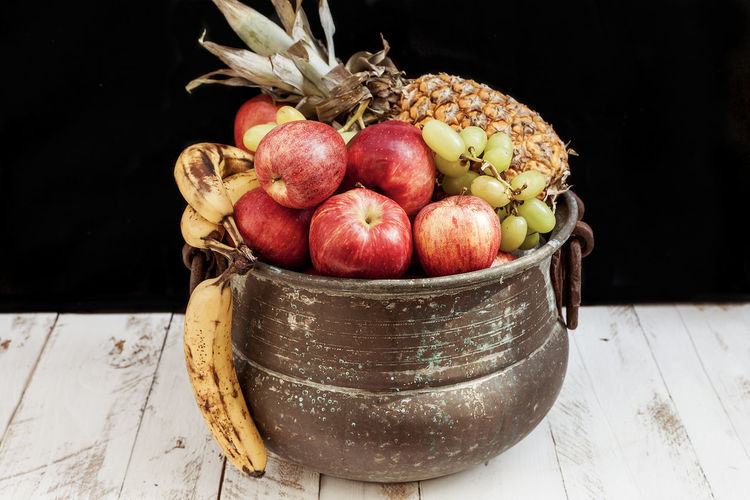Close-Up Of Fruits In Container On Table Against Black Background