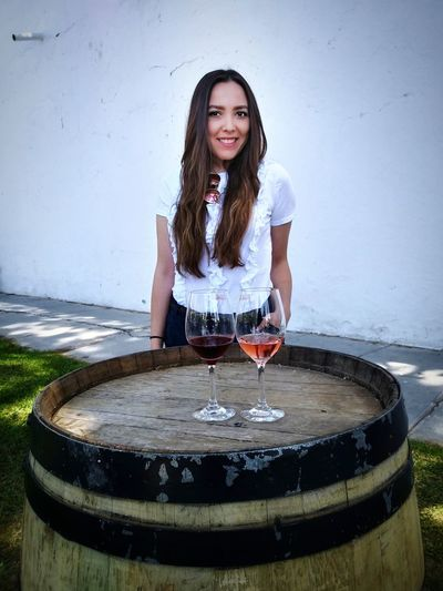 Portrait of smiling young woman standing by wine cask