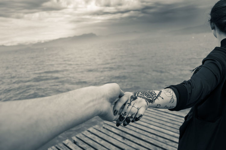 Cropped hand on man holding girlfriends hand while standing on pier against cloudy sky